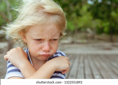 Face portrait of annoyed and unhappy caucasian kid with crossed arms. Upset and angry child concept for family relations, social problems issues and juvenile psychology.  Copy space outdoor background