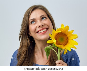 face portrait of happy woman holding sunflower in front of face.