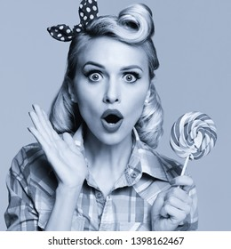 Face portrait photo of young excited woman with lollipop, dressed in pin-up style plaid shirt. Caucasian blond girl posing in retro fashion and vintage concept. Black and white picture. Square image.