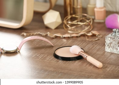 Face powder with brush and accessories on dressing table