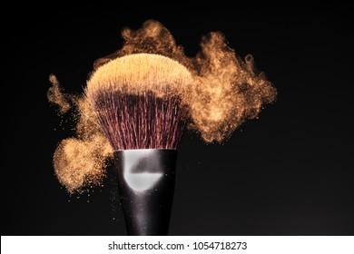 Face powder on a single make-up brush, freeze motion on black background