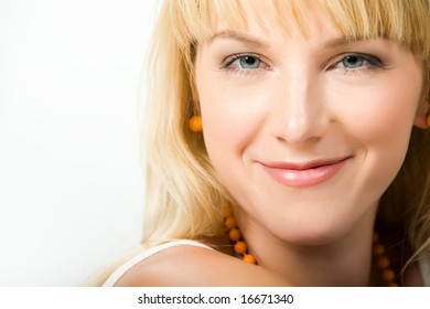 Face of pretty girl wearing orange earrings and beads and looking at camera with smile