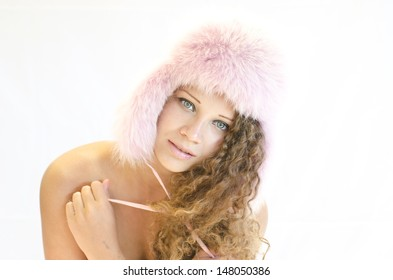 Face of pretty woman in pink winter cap looking at camera with smile