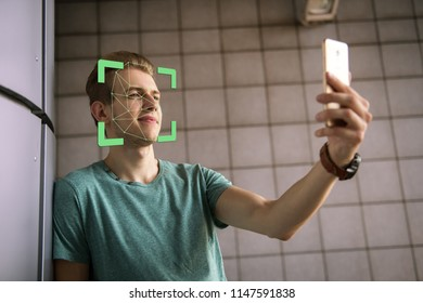 Face recognition. Biometric verification. The concept of a new face recognition technology on a polygonal mesh. Young modern guy with a smartphone in his hands. Young man with phone in hands.