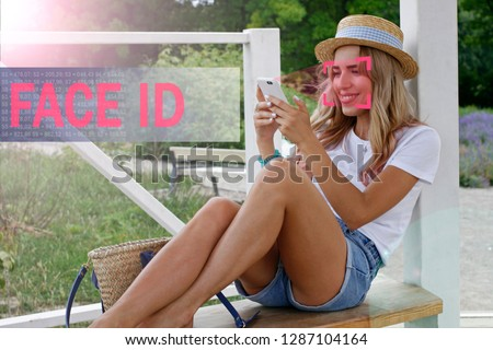 Face recognition. Biometric verification. The concept of new face recognition technology. Young modern girl. Young girl with a phone in her hands