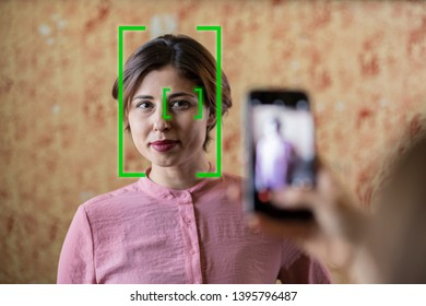 face recognition technology activated while taking a photo of a young woman with mobile phone