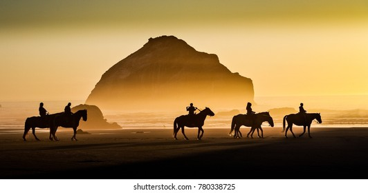Face Rock, with horses and riders, and other sea stacks at sunset on the southern Oregon coast at Bandon