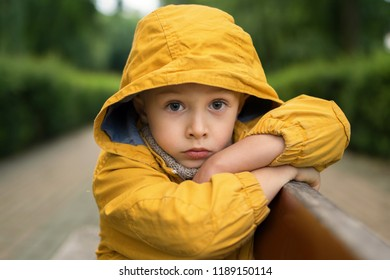 The face of a sad, little boy, with big beautiful eyes, in a park on a bench, in a yellow jacket with a hood on his head. Concept of children's fear, guilt, longing. Waist up portrait.