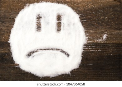Face of a sad smiley made with granulated sugar. The picture illustrates the harm of eating sugar and salt, as well as dependence on flavoring additives.