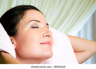 Face of serene female with her eyes closed drying hair with soft towel