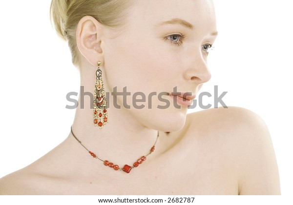 Face shot of beautiful fashion model with red jewelery