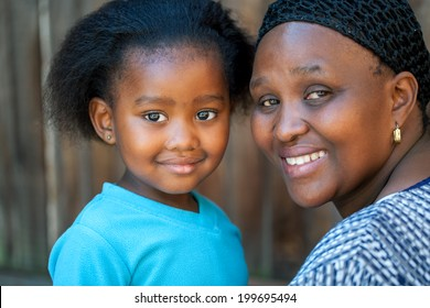 Face shot of little African girl with mom outdoors.