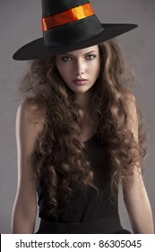 face shot of a young and beautiful girl dressed up for halloween with a huge black witch hat looking straight into the cam