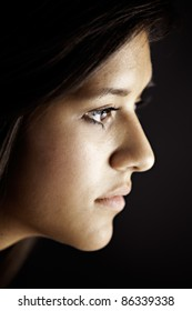 Face side view of a cute pretty teenage female girl isolated against a black background