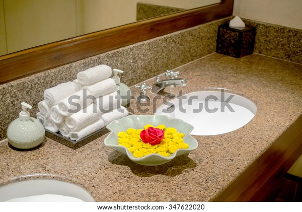 Face sink in the hotel with decoration using stuff such as soap , towels , tissue and flower decoration