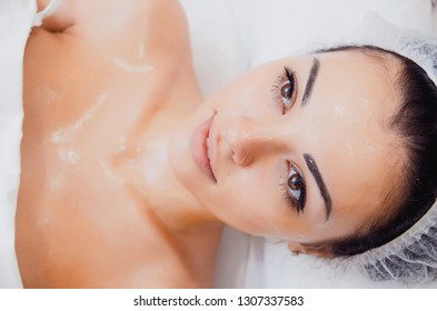 Face Skin Care. Beautician Applying Beauty Oil Mask On Face Using Brush In Spa Salon. Closeup Of Female Client Getting Hydrating Procedure In Beauty Clinic. Cosmetology