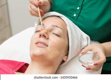 Face skin care. Beautician applying beauty oil mask on face using brush In spa salon