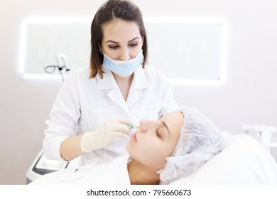Face skin care. Portrait of beautiful young doctor with syringe near female face. Cosmetic beauty spa clinic. Biorevitalization of the face procedure