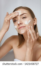 Face skin care. Woman applying facial cleanser on face closeup. Girl using cleansing cosmetic product on skin, washing face on light background