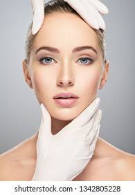 Face skin check before plastic surgery. Beautician touching woman face. Perfect shape of female face.
