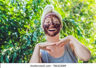 Face Skin Scrub. Portrait Of Sexy Smiling Female Model Applying Natural Coffee Mask, Face Scrub On Facial Skin. Closeup Of Beautiful Happy Woman With Face Covered With Beauty Product. High Resolution.
