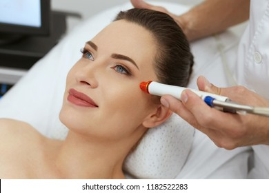 Face Skin Treatment. Woman Doing Skin Microdermabrasion Therapy