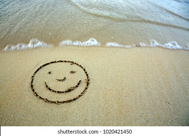 Face smail drawing in the sand at the caribbean beach.