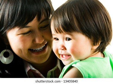 Face of smiling little girl with her loving mother at the background