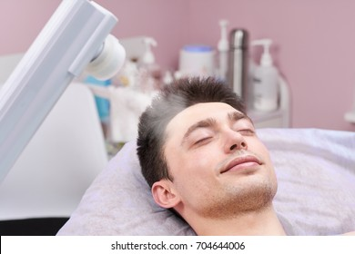 Face steaming in cosmetology clinic. Healthy man with eyes closed.