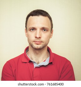 Face studio portrait of young adult European man in red polo shirt, square frame