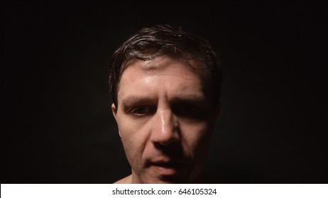 Face of sweating man in dark room