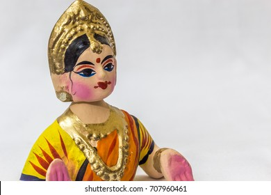 Face of a Thanjavur dancing doll (Called as Thalaiyatti Bommai in Tamil language) with look alike traditional dress and ornaments in a white background