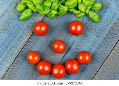 A face of tomatoes and basil on blue wood