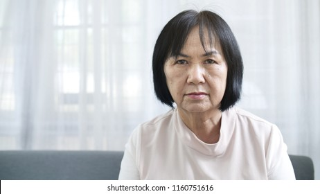 Face of unhappy lonely Asian senior woman sitting alone at home