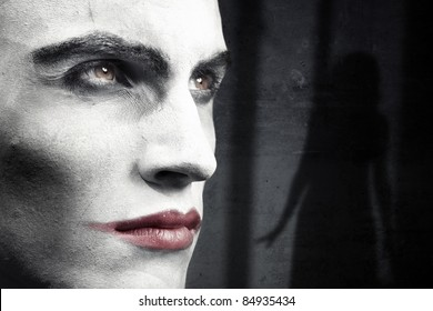 Face of vampire on a dark grungy background with woman shadow