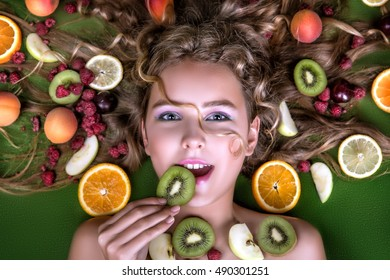 The face is very beautiful young blonde girls with big fruit and berries in her hair: orange, lemon, kiwi, peach, plum, raspberry, apricot. Summer, green background. Soft skin.