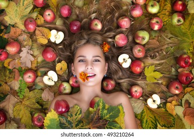 The face is very beautiful young blonde girls with big fruit and apples in the hair: apples, autumn leaves. AUTUMN Soft leather