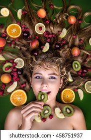 The face is very beautiful young sweet girl blonde .Lezhit with fruit and berries in her hair: peaches, kiwi, plum, raspberry, orange, lemon,