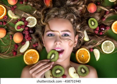 The face is very beautiful young sweet girl blonde .With fruit and berries in her hair: peaches, kiwi, plum, raspberry, orange, lemon,