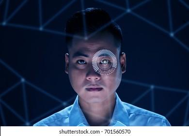 Face of Vietnamese man using modern technology to scan his retina