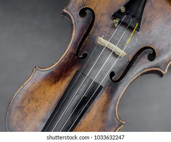 face of violin with snares against gray background in closeup