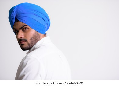 Face of young bearded Indian Sikh man wearing turban and looking back