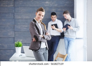 Face of young beautiful business woman on the background of business people in modern office. Young start up concept.