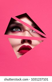 the face of a young beautiful girl with a bright make-up and with plump red lips peeks into a hole in pink paper.Fashion, beauty, cosmetics, make-up, beauty salon, make-up artist, sales, business.