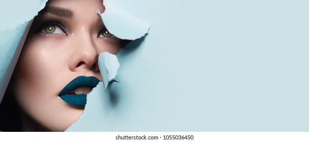 the face of a young beautiful girl with a bright make-up and puffy blue lips peers into a hole in blue paper.Fashion, beauty, make-up, cosmetics, hairstyle, beauty salon, boutique, discounts, sales.
