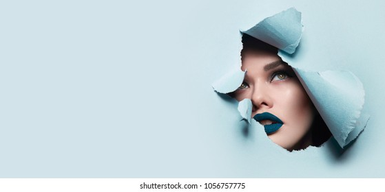 the face of a young beautiful girl with a bright make-up and puffy blue lips peers into a hole in blue paper.