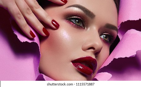 The face of a young beautiful girl with a bright make-up and with plump red lips peeks into a hole in pink paper. Nails with bright red lacquer.