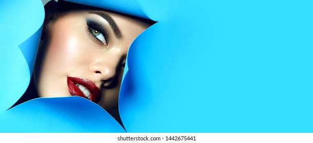 The face of a young beautiful girl with bright makeup and plump red lips looks into the hole in blue paper. Fingers with natural color varnish.