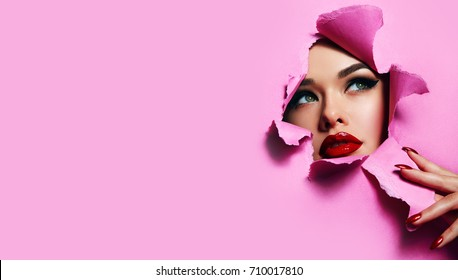 the face of a young beautiful girl with a bright make-up and with plump red lips peeks into a hole in pink paper. Nails with bright red lacquer.Lipstick,cosmetics,makeup, fashion, beauty,beauty salon.