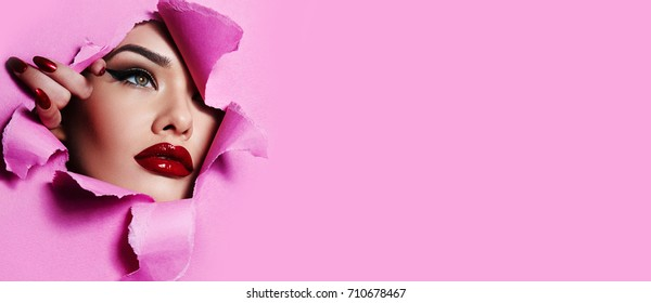 the face of a young beautiful girl with a bright make-up and with plump red lips peeks into a hole in pink paper.Beauty, fashion, personal care,cosmetics, make-up,health, beauty salon, make-up artist.
